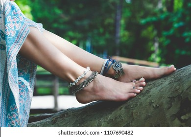 woman summer boho fashion style details on barefoot anklets and rings outdoor  lean on tree
