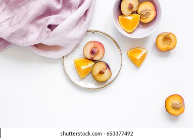 woman summer breackfast with orange and peach fruits and fabric on white background flat lay mockup