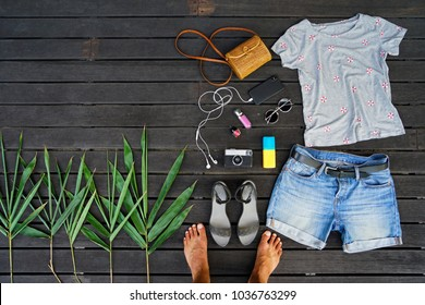 Woman summer clothes collage flat lay isolated on dark wood background. Feminine desk top view fashion accessories: t-shirt, shorts, sandals, sunglasses, vintage photo camera, headphones, legs. Travel