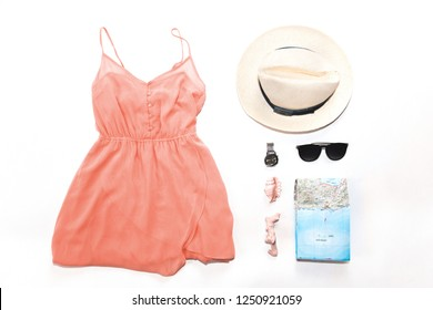 woman summer clothes collage on white, flat lay, top view. dress, card, straw hat, Sunglasses. Color of the year 2019 Living coral