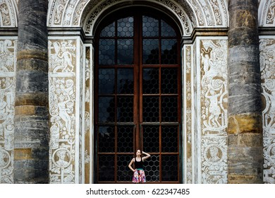 Woman in summer dress standing in middle of huge entrance window of historic building. Window has structure with wooden frames. On sides are massive stone pillars embedded in wall with paintings.