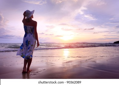 Woman in summer dress standing on a sandy beach and looking to the horizon