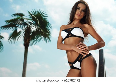 Woman Summer Fashion. Beautiful Girl Model With Fit Body, Tanned Skin Wearing Fashionable Women Bikini, Tropical Sky On Background. Female In Sexy Swimwear Tanning At Luxury Resort. High Resolution