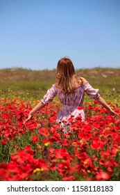 Woman in a summer field among red poppies