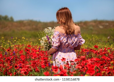 Woman in summer field with bouquet of flowers