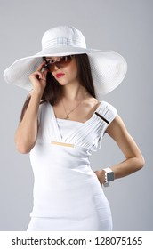Woman in summer outfit in studio. Fashion woman wears white hat with large fields and sunglasses.