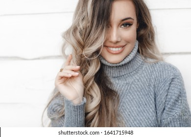 woman summer portrait. shining smiling girl outdoors. fashion and beauty. young girl in autumn colors posing near white wall smiling. Autumn woman. Brown hair and eyes. Warm autumn. Warm sunny spring