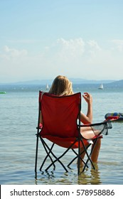 A woman in the sun chair on the beach of a lake