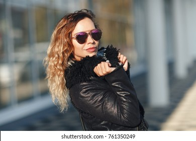 woman in sun glasses a black leather jacket, black jeans posing in front of mirrored windows. Female fashion concept. Outdoor.
