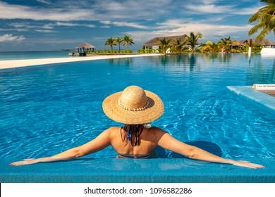 Mujer con sombrero de sol en la piscina de playa en Maldivas