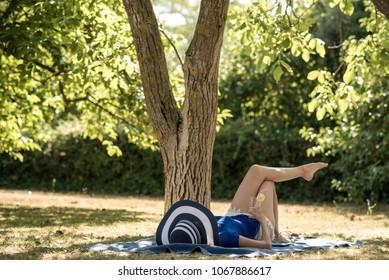 Woman in a sun hat relaxing on a grass in summer lying on a rug in the shade of a tree with a refreshing drink in her hand.