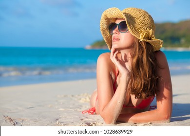 woman in sun hat and swimsuit at beach. Praslin, Seycheles