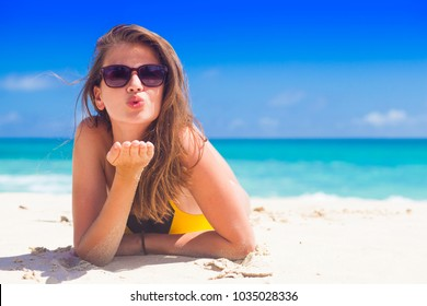 woman in sun hat and swimsuit at beach. blowing a kiss
