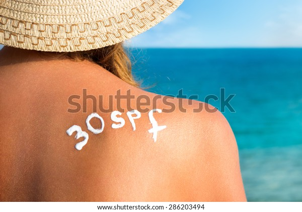 Woman with  sun tan cream in form  of SPF 30 word on her back over sea background