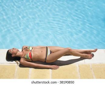 Woman sunbathing around swimming pool