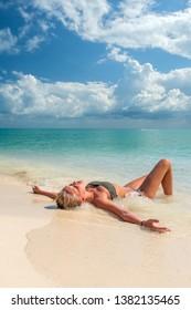 woman sunbathing lying down on the tropical beach summer travel holidays