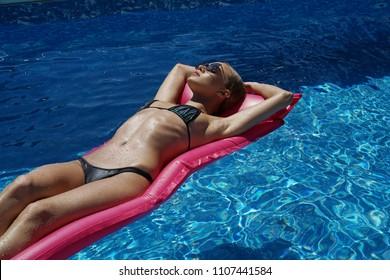 Woman sunbathing on air mattress - swimming in the pool