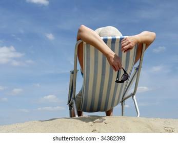 Woman sunbathing on deckchair on the beach shot against blue sky