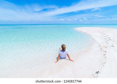 Woman sunbathing on scenic white sand beach, rear view, sunny day, turquoise transparent water, real people. Indonesia, Wakatobi islands