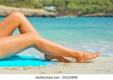 Woman sunbathing on tropical beach. Legs.