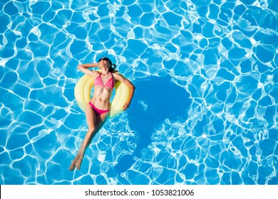 Woman sunbathing on yellow rubber ring in the pool
