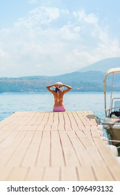 Woman with sunburned back sit on wooden jetty while looking at the sea. Selective focus. Vertical image.Copy space. Summer vacation in Europe.