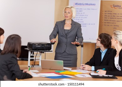 Woman sung a projector giving a corporate training class to a group of young businesspeople around a table gesturing with her hands as she explains something