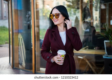Woman in sunglases with cup of coffee in cafe outdoors