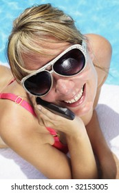 Woman in sunglasses besides a bright blue swimming pool talking into her mobile phone