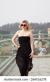woman in sunglasses in black dress in the city