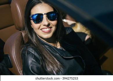 Woman with sunglasses in a convertible car
