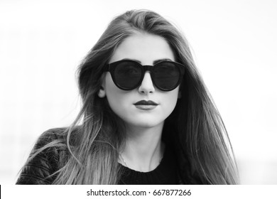 Woman in sunglasses head - portrait. Long haired girl's portrait on light background, street style, beauty, casual, black and white look. Feminine, fashion, stylish people.
