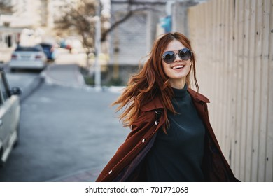 Woman in sunglasses on the street in the city in autumn.