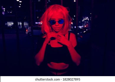 woman in sunglasses in red light at night outdoors
