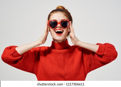 woman in sunglasses in the shape of a heart red sweater