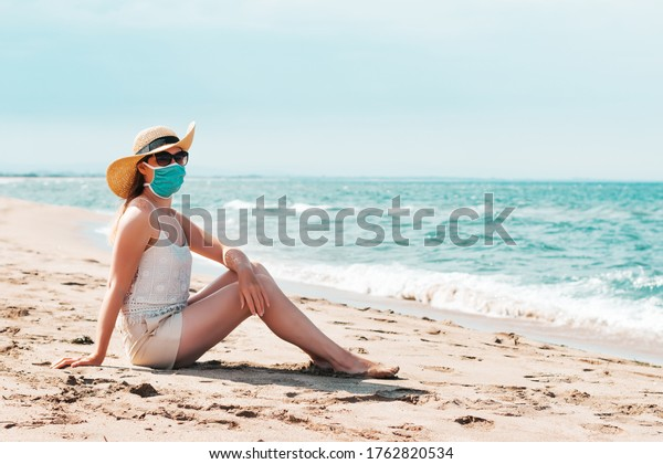 Woman in sunglasses and straw hat wearing medical mask at beach, new normal rules, web banner. Life after pandemic, obligatory use of face mask in public spaces, copy space