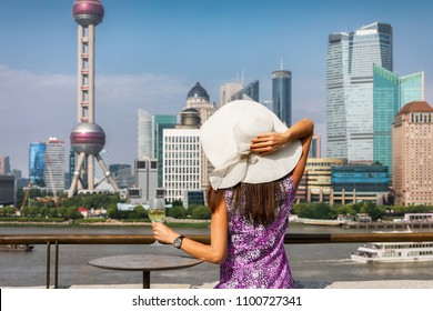 Woman with sunhat enjoys a glass of wine in front of the skyline of Shanghai during a beautiful spring day, China
