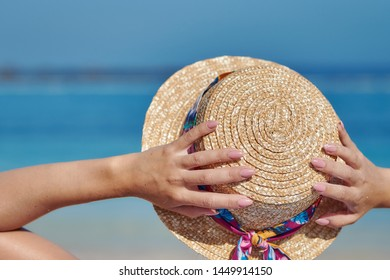 Woman in sunhat relaxing on beach during summer vacation. Back view.