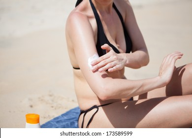 woman with sunscreen on the beach