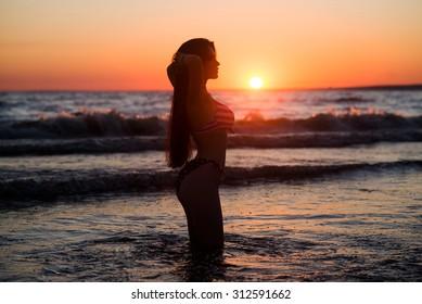 Woman, sunset, fashion model on the beach. Sea
