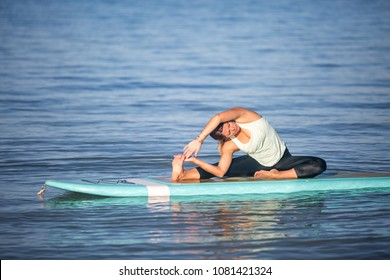 Woman in SUP Yoga practice on the ocean in Hawaii