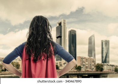 Woman superhero with red cape in the city. Vintage color.
