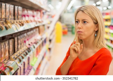 Woman in supermarket aisle choosing products