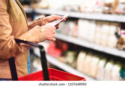 Woman in supermarket aisle with food shelf reading shopping list and holding basket. Woman buying groceries in store. Retail, sale and consumerism concept.