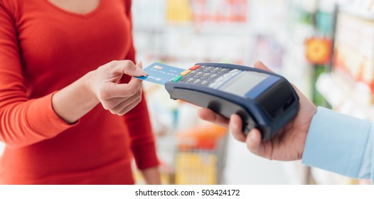 Woman at the supermarket checkout, she is inserting her credit card in the terminal, shopping and retail concept