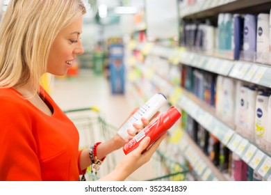 Woman in supermarket comparing two products