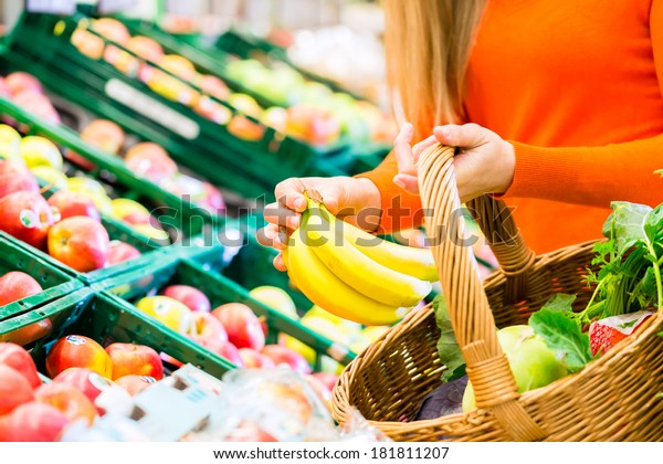 Woman in supermarket at the fruit shelf shopping for groceries, she is putting a banana in her basket