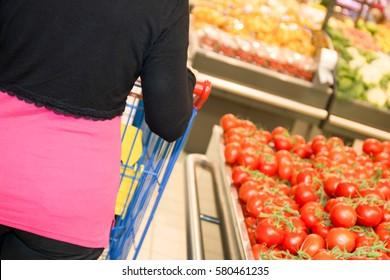 Woman at supermarket pushing a shopping cart