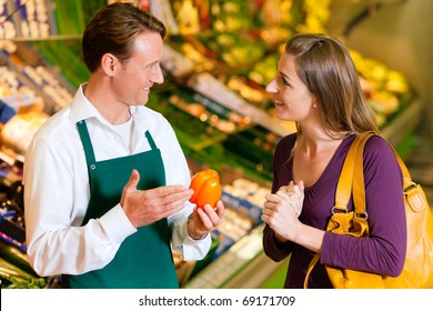 woman in a supermarket at the vegetable shelf shopping for groceries, a shop assistant is helping her