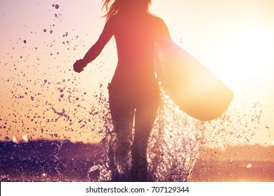 Woman with surfboard runs from the ocean during sunset